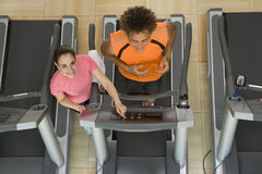 Fitness instructor training man on treadmill in gym, portrait, elevated view Royalty Free Stock Photography