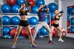 Kettlebell workout in the gym. Fitness instructor with two girls working out with kettlebell Stock Images