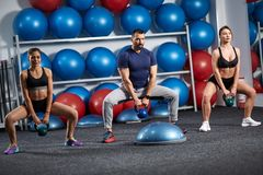 Kettlebell workout in the gym. Fitness instructor with two girls working out with kettlebell Royalty Free Stock Images