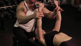 Fitness instructor working with a young girl in the gym stock footage