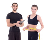 Fitness instructor and young beautiful woman with measuring tape. Fitness instructor and young beautiful women with measuring tape isolated on white background Stock Photo