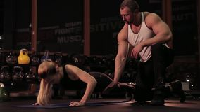 Fitness instructor and young woman in gym stock video