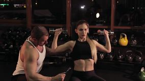 Fitness instructor with a young woman in the gym stock video footage