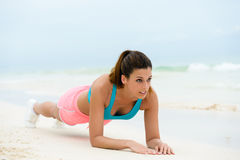Fitness isometric plank exercise. Fitness woman doing plank isometric core exercise. Female athlete working out midsection on summer vacation at the beach stock images