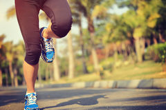 Fitness jogger legs running at tropical park Royalty Free Stock Photo