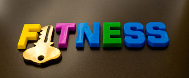 Fitness: the key. A macro image of the word fitness in colorful upper case letters with the letter 'I' replaced with a gold key. The image is isolated on a dark Royalty Free Stock Image