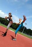 Fitness Kicking exercises. Two women doing fitness kicking exercises stock image