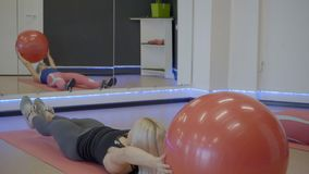 Fitness ladies doing abdominal crunches with ball in sports club. They lay on gymnastic mat then straining abs muscles, raise legs and arms up, keeping fitball stock footage