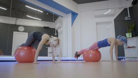 Fitness ladies doing exercise with balls in sports club. Two people lean on fitball with legs then move, lifting buttocks up and lowering head down. Attractive stock video
