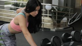 Fitness lady doing dumbbell row exercise in sports club. Female leans on metal rack with hands and pulls free weight, bending elbow, then returns to starting stock footage