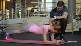 Fitness lady doing plank exercise with trainer in sports club. Fitness lady doing plank exercise with trainer in sports club stock video