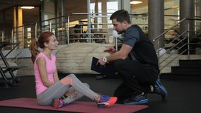 Fitness lady talks to male instructor in gym room. Woman sits on gymnastic mat and communicates to man who takes notes with pen on paper, writing training stock video