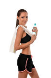 Fitness lady with towel over her shoulder and a bottle of water Royalty Free Stock Image