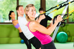 Fitness - Leute beim Suspension training. Group of people exercising with suspension trainer in fitness club or gym Stock Photos