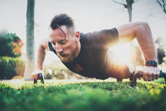 Fitness lifestyle concept.Muscular athlete exercising push up outside in sunny park. Fit shirtless male fitness model in Stock Photography