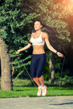 Fitness and lifestyle concept - woman doing sports. Outdoors. girl with skipping rope Royalty Free Stock Photo