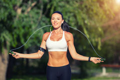 Fitness and lifestyle concept - woman doing sports. Outdoors. girl with skipping rope Royalty Free Stock Images