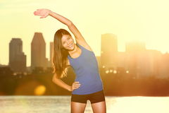 Fitness lifestyle : happy woman stretching in city Stock Photography