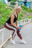 Fitness lifestyle. Sporty young woman sitting on railing and holding a water bottle after a workout. Workout at the stadium. royalty free stock images