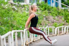 Fitness lifestyle. Young woman doing push ups from the pillar. Sporty young blonde girl on a sunny day at the stadium. Healthy. Life concept. Horizontal photo stock photography