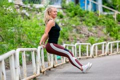 Fitness lifestyle. Young woman doing push ups from the pillar. Sporty young blonde girl on a sunny day at the stadium. Healthy royalty free stock images