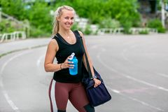 Fitness lifestyle. Young woman holding a water bottle and a bag on her shoulder after a workout. Workout at the stadium. Healthy royalty free stock image