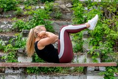 Fitness lifestyle. Young woman warming up on a bench, doing exercises on abdominal muscles. Sporty young blonde girl on a sunny stock photo