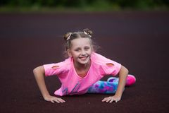 Fitness little girl resting after exercises at stadium. Sport girl posing at stadium. Fitness girl with a sports figure in royalty free stock photo