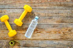 Fitness for loosing weight. Dumbbells, measure tape and water on wooden background top view copyspace Stock Images