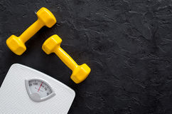 Fitness for losing weight. Bathroom scale and dumbbell on black background top view stock photos