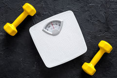 Fitness for losing weight. Bathroom scale and dumbbell on black background top view stock photography