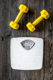 Fitness for losing weight. Bathroom scale and dumbbell on wooden background top view royalty free stock photography