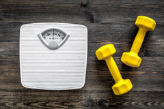 Fitness for losing weight. Bathroom scale and dumbbell on wooden background top view stock photography