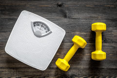 Fitness for losing weight. Bathroom scale and dumbbell on wooden background top view royalty free stock photo