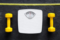 Fitness for losing weight. Bathroom scale, measuring tape and dumbbell on black background top view. Fitness for losing weight. Bathroom scale and dumbbell on Stock Photos