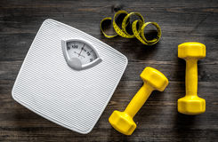 Fitness for losing weight. Bathroom scale, measuring tape and dumbbell on wooden background top view Royalty Free Stock Photography