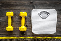 Fitness for losing weight. Bathroom scale, measuring tape and dumbbell on wooden background top view stock photos
