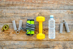 Fitness for losing weight. Dumbbells, expander, measure tape and water on wooden background top view copyspace Stock Photos