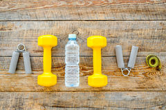 Fitness for losing weight. Dumbbells, expander, measure tape and water on wooden background top view copyspace Royalty Free Stock Images