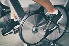 Free Fitness Machine At Home Woman Biking On Indoor Stationary Bike Exercise Indoors For Cardio Workout. Closeup Of Shoes On Royalty Free Stock Photos - 176745668