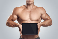 Fitness male holding horizontally digital tablet with blank scre royalty free stock image