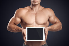 Fitness male holding horizontally digital tablet with blank scre Stock Photos