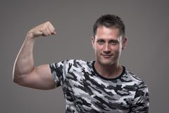 Fitness male model in army shirt flexing arm and showing bicep muscles. Portrait of athletic muscular fitness male model in army shirt flexing arm and showing stock photos