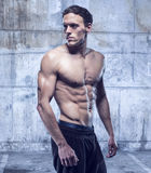Fitness male model in old garage Royalty Free Stock Photography