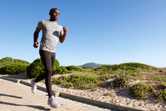 Fitness male model running at the beach. Full length portrait of fitness male model running on the boardwalk at the beach Royalty Free Stock Images