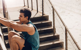 Fitness male stretching outdoors at the beach. Fitness male doing stretching workout outdoors at the beach. Healthy young man stretching on a railing Royalty Free Stock Photography