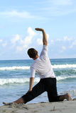 Fitness man. Man doing stretching exercises on the beach Stock Photo