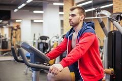 Fitness man on bicycle doing spinning at gym. Fit young man working out on gym bike. Stock Photos