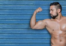 Fitness man with blue wood background. Digital composite of fitness man with blue wood background Royalty Free Stock Image