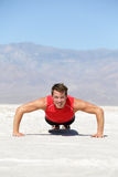 Fitness man crossfit training push-ups in desert royalty free stock images